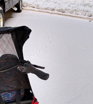 photo of the corner of an urban arrow cargo bike and some turkey tracks in snow